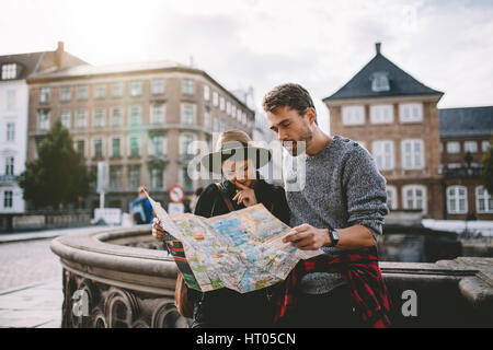 Young couple looking at a navigation map of the city. Tourists finding their way looking at a map standing on the - Stock Photo