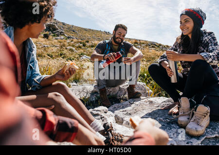 Group of hikers couple eating sandwiches and drinking coffee while relaxing in field. Young people having a rest - Stock Photo