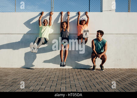 Group of people having fun during workout session outdoors. Friends hanging to a wall and stretching after running - Stock Photo