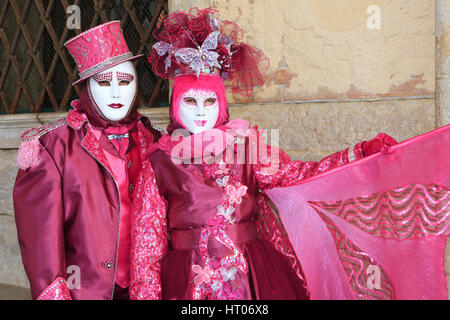 A couple in pink costumes outside the Doge's Palace during the Carnival of Venice, Italy - Stock Photo