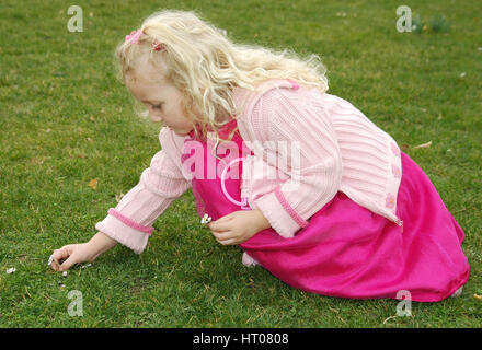 Maedchen pflueckt Gaensebluemchen in der Wiese - girl plucks daisies in meadow - Stock Photo