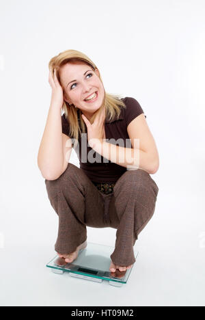 Froehliche Frau auf Waage - happy woman on scale - Stock Photo