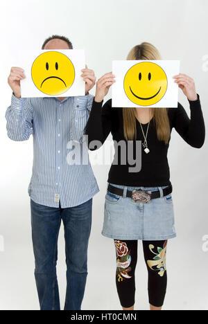 trauriger Mann, lachende Frau, Symbolbild unausgeglichene Partnerschaft - sad man, lucky woman - Stock Photo