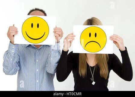 lachender Mann, traurige Frau, Symbolbild unausgeglichene Partnerschaft - sad woman, lucky man - Stock Photo