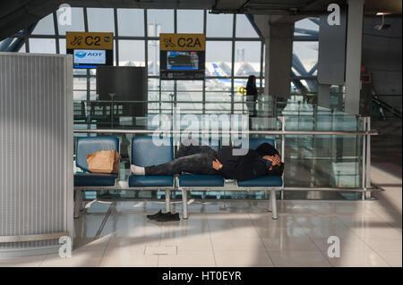 08.02.2017, Bangkok, Thailand, Asia - A man sleeps in the departure area at Bangkok's Suvarnabhumi Airport. - Stock Photo