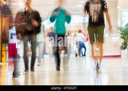 Abstract defocused motion blurred young people walking in the shopping center, urban lifestyle concept, background. - Stock Photo