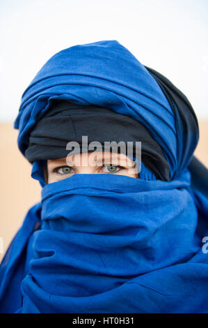 A woman with Blue Eyes wearing a blue headscalf in the Sahara Desert, Morocco - Stock Photo
