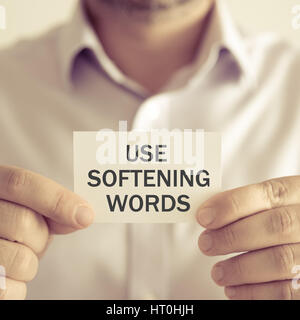 Closeup on businessman holding a card with text USE SOFTENING WORDS, business concept image with soft focus background - Stock Photo