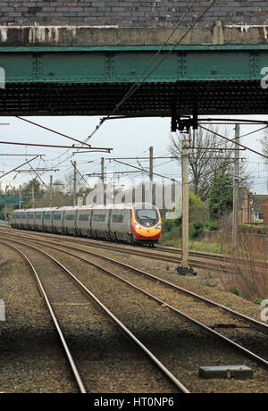 A Virgin West Coast Pendolino approaches Euxton Balshaw Lane station near Leyland at speed as a Glasgow Central - Stock Photo