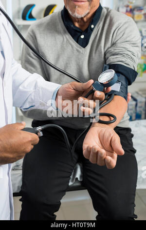 Cropped image of male chemist checking blood pressure of senior patient in pharmacy - Stock Photo