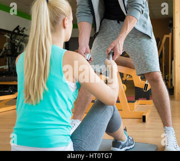 Personal trainer handing dumbbells to young woman during workout session - Stock Photo