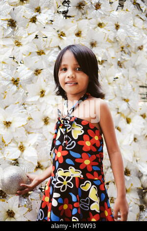 Beautiful little girl standing right near the white giant christmas tree - Stock Photo