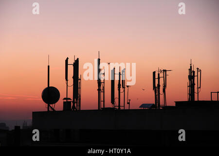 silhouette of GSM transmitters on the roof office building at dusk - Stock Photo
