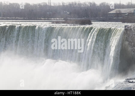 Niagara Falls on the Canadian US border in winter.  Coulds of frozen spray in the air. - Stock Photo