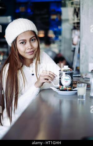 Beautiful young girl wearing white clothes driniking tea in a bar - Stock Photo