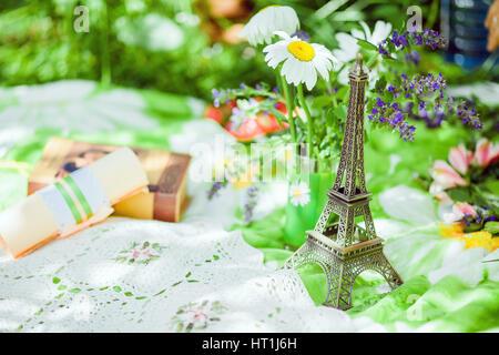 Eiffel Tower Souvenir on green picnic - Stock Photo