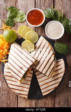quesadilla with meat, spinach and cheddar cheese close-up on the table. vertical view from above - Stock Photo