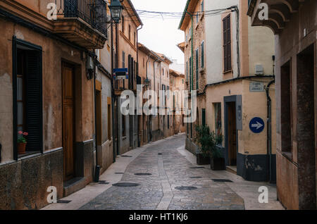 Narrow winding streets in historical town part of Pollensa with its traditional stone houses, Mallorca, Spain - Stock Photo