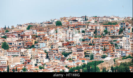Aerial panoramic view of the colorful Thessaloniki city. Houses with red tile roofs are arranged in rows on a hill. - Stock Photo