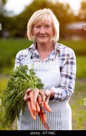 Older woman showing domestic grown carrots in garden