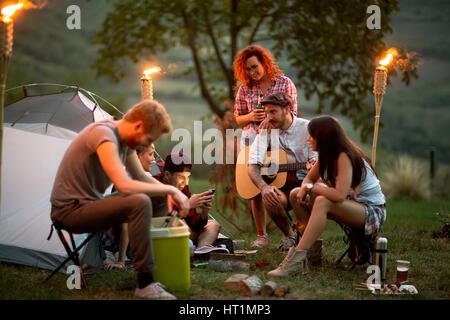 Group of young people at night in campground look at photos on mobile - Stock Photo