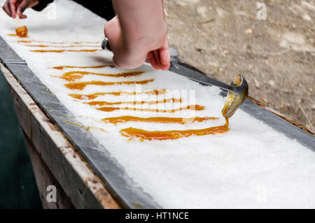 Maple taffy on snow during sugar shack period. In Quebec, Canada. - Stock Photo