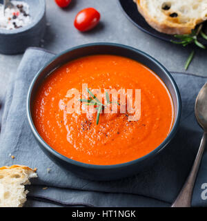 Tomato soup in a black bowl on grey stone background. - Stock Photo