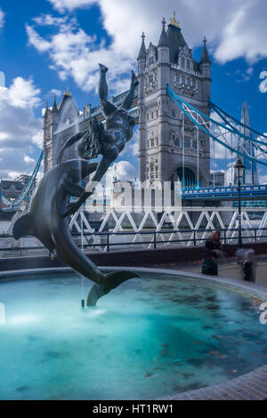 The 'Girl with a Dolphin' sculpture by David Wynne, on the north bank of the River Thames, with Tower Bridge in - Stock Photo
