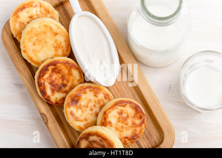 Homemade cottage cheese pancakes on white wooden table served with sour cream. Syrniki, traditional Ukrainian cuisine - Stock Photo