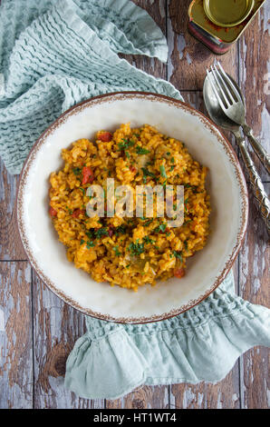 Spanish paella with artichokes and roasted red peppers - Stock Photo