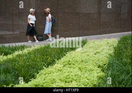 17.09.2016, Singapore, Republic of Singapore - Two young women chat at the roadside near Raffles Place. - Stock Photo