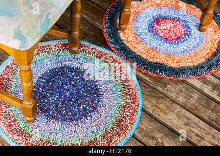 Two handmade colorful rugs on a wooden floor with a pair of chairs - Stock Photo
