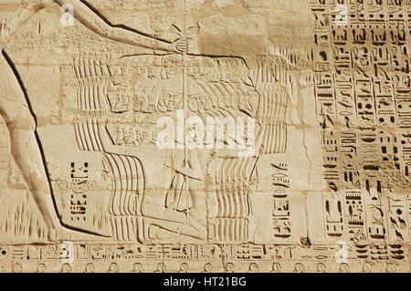 Detail of a relief on the mortuary temple of Ramesses III depicting the pharoah smiting his enemies. Artist: Werner - Stock Photo