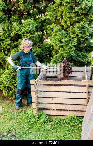Young caucasian female tumbling the compost with a pitch fork - Stock Photo