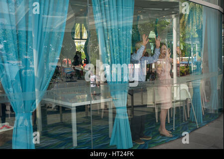 02.10.2016, Singapore, Republic of Singapore - People wave at children on the street from inside a restaurant at - Stock Photo