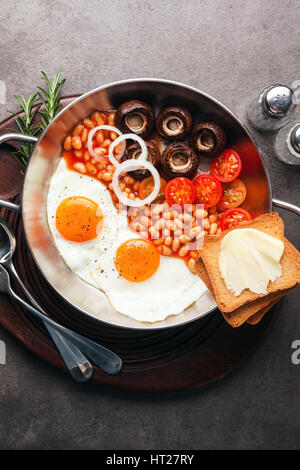 sunny side up Egg with mushrooms, tomatoes and bean in  skillet pan on grey stone background - Stock Photo