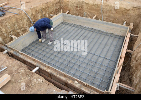 A big hole of pole in construction site building prepare for pouring cement.Worker controlled steel - Stock Photo