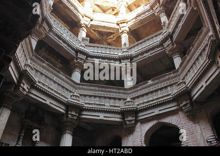 Upper storeys with intricate stone carvings on pillars, pilaster and entablature. Adalaj Stepwell, Ahmedabad, Gujarat, - Stock Photo