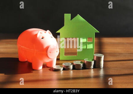 Saving money to buy house or home. Piggy bank with coins - Stock Photo