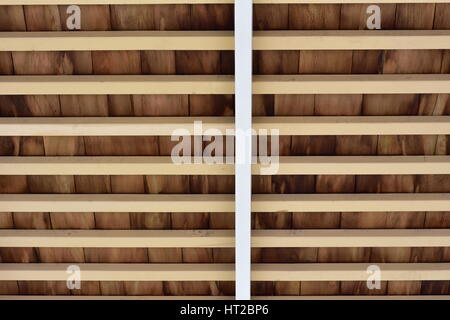 Rustic wooden ceiling showing horizontal beams and rows of wooden shingle. - Stock Photo