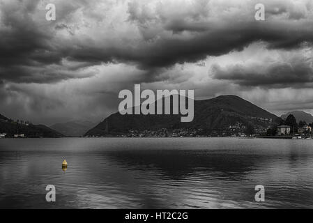 cloudy afternoon over the Lugano Lake with yellow floating buoy, Porto Ceresio - Varese - Italy - Stock Photo