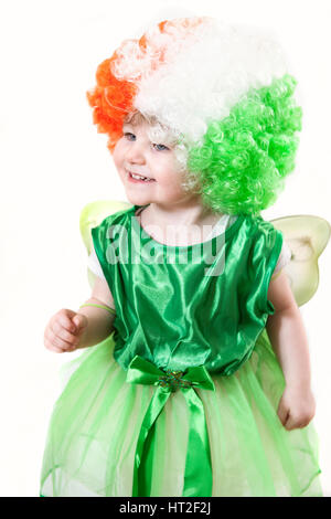 A crop of a cute girl in a green dress with a shamrock, fairy wings and a wig with the colors of the Irish flag - Stock Photo