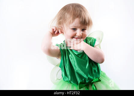 A cute little girl in a green dress and fairy wings ready to celebrate Saint Patrick's Day - Stock Photo