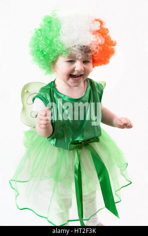A cute little girl dressed in a green dress with a shamrock, fairy wings and a wig with the colors of the Irish - Stock Photo
