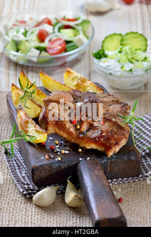 Greek meal: Fried lamb chops with baked potato wedges, farmers salad and tzatziki - Stock Photo