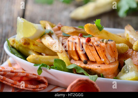 Roasted  white asparagus with fried salmon served on rocket salad leaves in a white bowl - Stock Photo