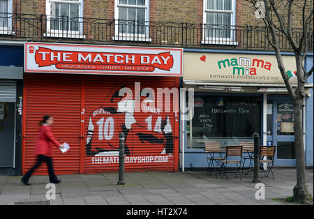 London, UK. 06th Mar, 2017. A woman walks past a fan shop called 'The Match Day' located next to the Emirates Stadium - Stock Photo