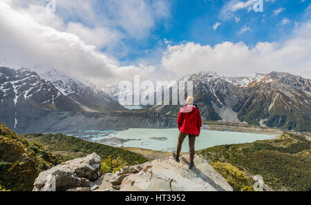 Hiker standing on rocks, view into the Hooker Valley from Sealy Tarns Track, glacial lakes Mueller Lake and Hooker - Stock Photo