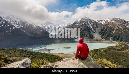 Hiker sitting on rocks, view into the Hooker Valley from Sealy Tarns Track, glacial lakes Mueller Lake and Hooker - Stock Photo