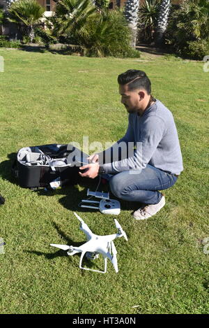 Licensed drone pilot flying DJI Phantom 4 Drone  with a gimbal and camera attached.  Drone, photography, video, - Stock Photo